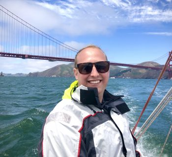 Torben Yjord-Jackson is pictured sailing. He is wearing a white jacket and the Golden Gate Bridge is pictured in the background.